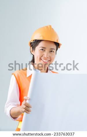 Cheerful architect holding a blank placard - stock photo