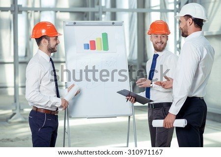 Cheerful architect is explaining to his team the main ideas of construction. He is pointing at blueprint with inspirations. The workers are smiling - stock photo