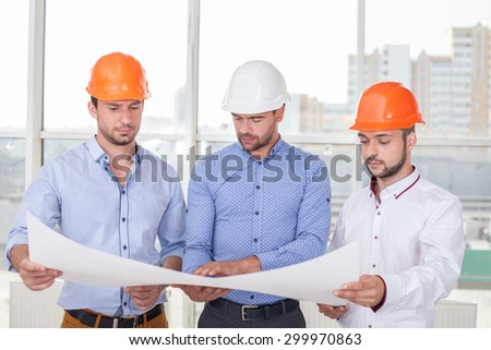 Cheerful architect is showing to builders the sketches o building. He is explaining the main ideas with seriousness. The men are looking at a paper with concentration - stock photo