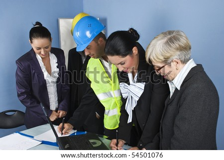 Cheerful architects and engineers having a  business meeting  in office and they writing and planning together - stock photo
