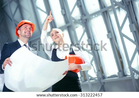 Cheerful architects are planning new project. They are holding a blueprint and smiling. The woman is standing and pointing her finger up with concentration. Copy space in right side - stock photo