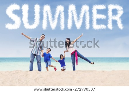 Cheerful asian family enjoy holiday on the beach under a summer's cloud - stock photo