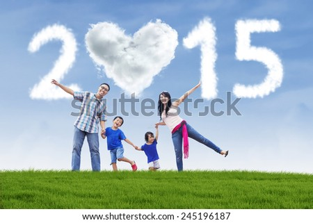 Cheerful asian family holding hands in meadow under cloud of 2015 - stock photo