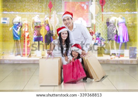 Cheerful asian family kneeling at shopping center while wearing christmas hat and holding shopping bags - stock photo