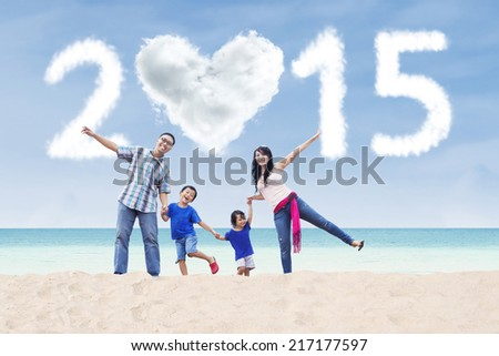 Cheerful asian family playing at beach under cloud of 2015 - stock photo
