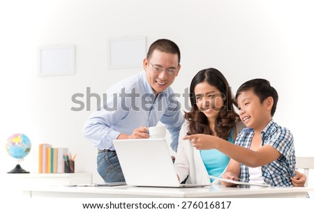 Cheerful Asian family watching something on laptop - stock photo