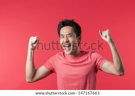 Cheerful Asian man celebrating with his arm up. In front of Red background. - stock photo