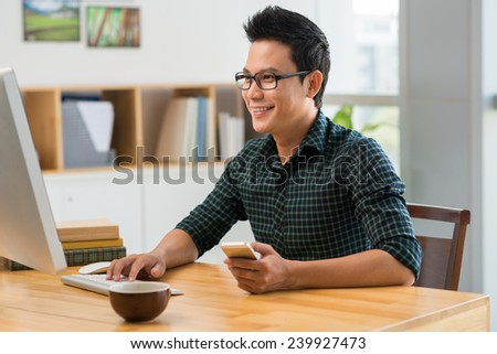 Cheerful Asian man with a cellphone in his hand and working on computer - stock photo