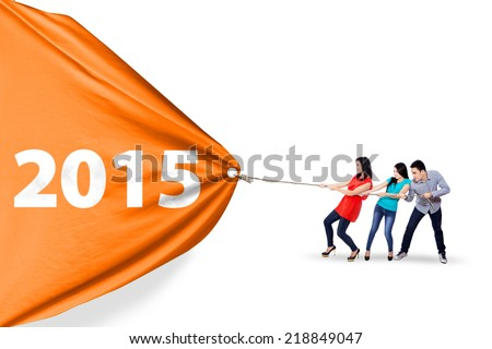 Cheerful asian people collaborate to pull a banner of 2015, isolated over white background - stock photo