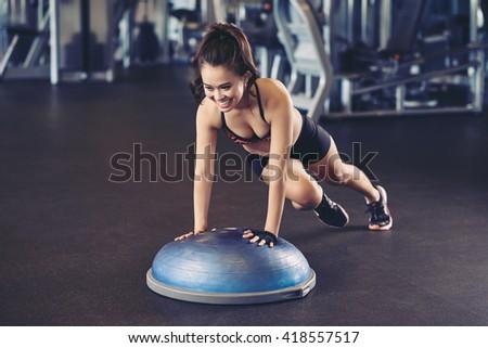 Cheerful Asian woman training with bosu ball - stock photo