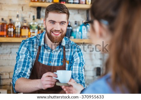 Cheerful attractive bearded barista serving cup of coffee to customer - stock photo