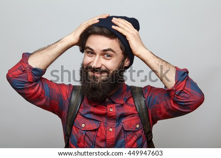 Cheerful attractive bearded young man with backpack isolated on grey background. Smiling male hipster holding hands on his head hat - stock photo