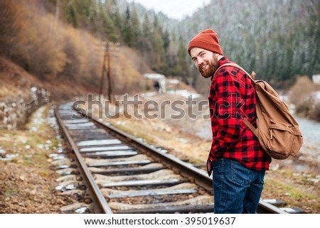 Cheerful attractive bearded young man with backpack walking along railroad in mountains - stock photo