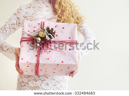 Cheerful attractive blond girl with gift box over wall background. Close up - stock photo