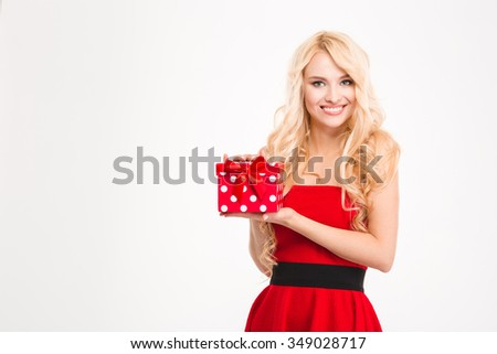 Cheerful attractive blonde female in red dress holding present isolated over white background - stock photo