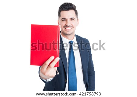 Cheerful attractive businessman giving  or offering a red book and smiling isolated on white studio background - stock photo
