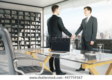 Cheerful attractive businessmen shaking hands in office with blank laptop, coffee cup and other items on glass desktop. Window with city view in the background. Mock up, 3D Rendering - stock photo