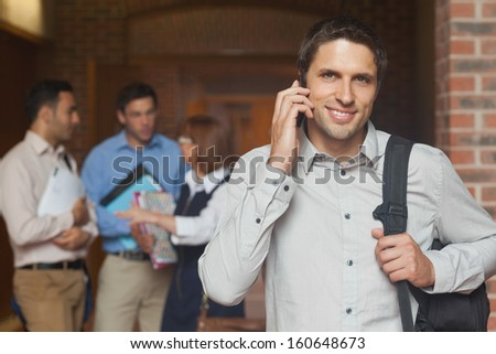 Cheerful attractive mature student phoning in corridor with his class in the background - stock photo