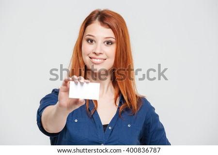 Cheerful attractive redhead young woman showing blank card over white background - stock photo