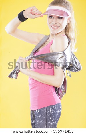 Cheerful attractive young fitness woman in sun visor on yellow background - stock photo