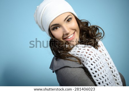 Cheerful attractive young girl smiling and looking at camera, in warm clothes and hat, toned - stock photo