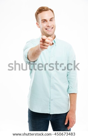 Cheerful attractive young man smiling and pointing at camera over white background - stock photo