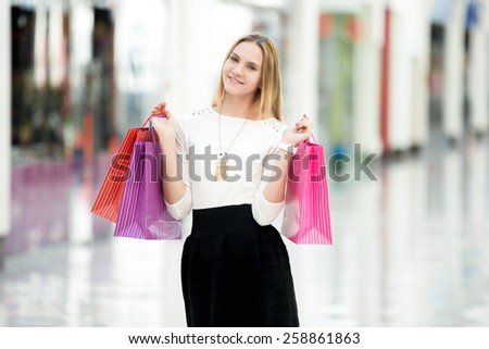 Cheerful attractive young woman enjoying shopping, holding bright colored paper bags beside boutiques in outlet, copyspace - stock photo