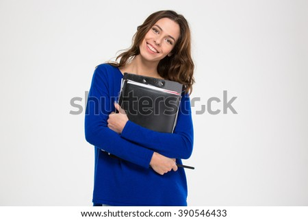 Cheerful attractive young woman standing and holding folders over white background - stock photo