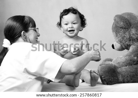 Cheerful baby at the doctor,playing with toy bear. - stock photo