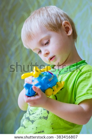 Cheerful baby blond boy playing a toy helicopter - stock photo