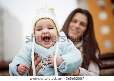 Cheerful baby boy having fun with his mother outdoors.Selective focus on baby. - stock photo