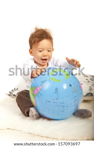 Cheerful baby boy playing with big world globe  - stock photo