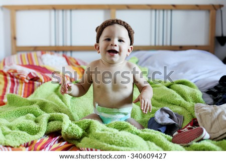 Cheerful baby child under a hooded towel after bathing - stock photo