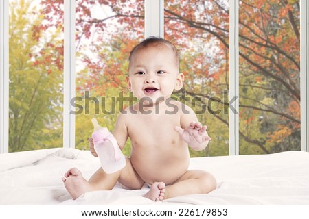 Cheerful baby girl holding a milk bottle on bedroom at home - stock photo