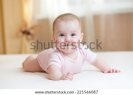 cheerful baby girl lying indoor - stock photo