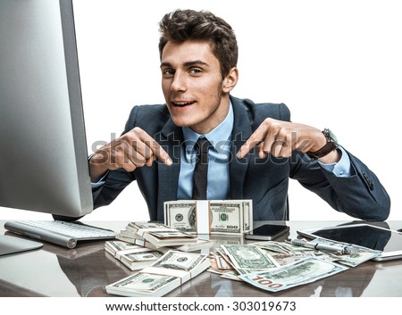 Cheerful banker showing his dividend profit, income, earnings, gain, benefit, margin / modern businessman at his desk with computer and a lot of money - stock photo