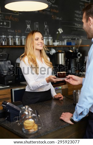Cheerful barista giving coffee cappuccino to client in coffee shop - stock photo