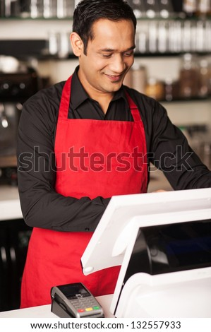 Cheerful barista staff cross-checking the order before billing the same. - stock photo
