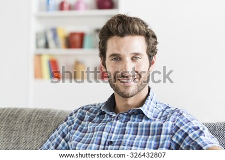 Cheerful bearbed hipster man in white modern house. Face camera - stock photo