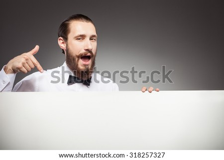 Cheerful bearded hipster guy is presenting white empty poster. He is pointing his finger at it. The guy is standing and laughing. Isolated on grey background and copy space in right side - stock photo
