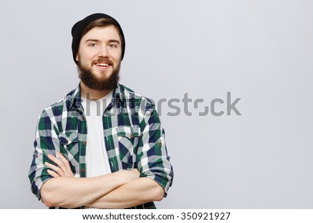 Cheerful bearded hipster, wearing on white t-shirt, black hat and blue checked shirt, posing on white background, in studio, waist up - stock photo