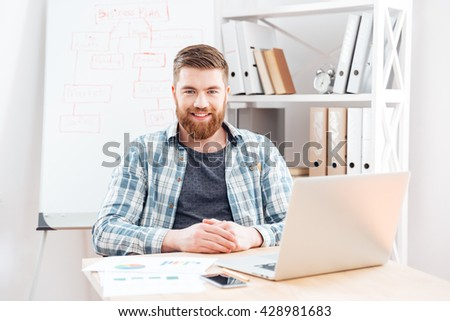 Cheerful bearded young businessman making business plan and working with laptop in office - stock photo