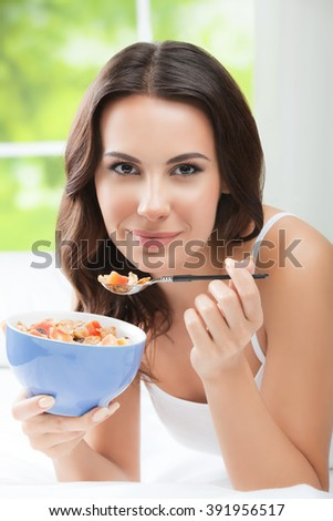 Cheerful beautiful brunette woman eating muslin, indoors. Healthy eating, beauty and dieting concept. - stock photo