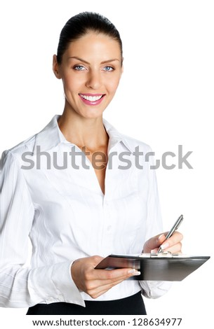 Cheerful beautiful business woman with clipboard writing, isolated over white background - stock photo