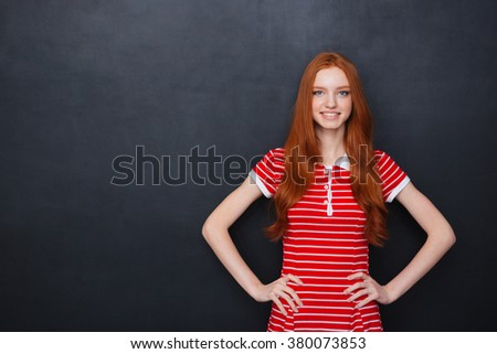 Cheerful beautiful redhead young woman smiling with hands on waist over blackboard background - stock photo
