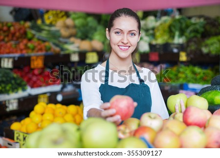 Cheerful beautiful sellers apples stacked on the counter and smiling - stock photo