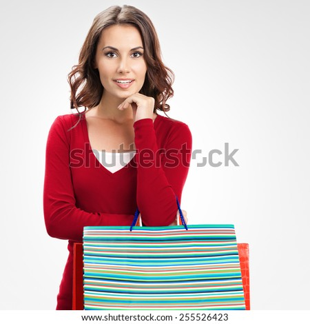 Cheerful beautiful woman in red casual clothing with shopping bags, over grey background - stock photo