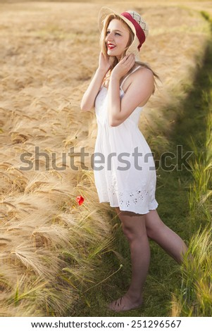 Cheerful beautiful young blonde blue eyes Scottish girl in white dress with straw hat posing at golden wheat field expressing happyness - stock photo