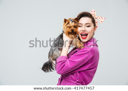 Cheerful beautiful young housewife having fun with dog - stock photo