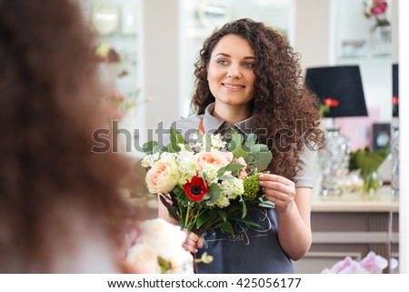 Cheerful beautiful young woman florist holding flower bouquet and looking at the mirror - stock photo